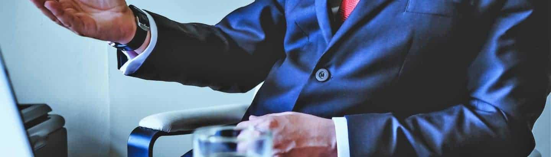 Verhandlungsdolmetscher im blauen Anzug vor Laptop