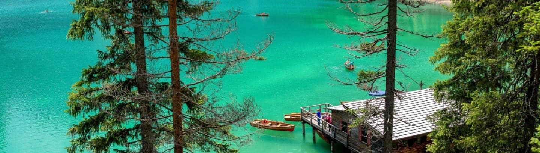 Tourismus Ziel an türkis-blauen See, mit Tannen, das auch eine Tourismus Übersetzung benötigt